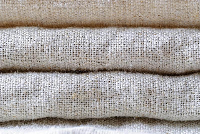 Neatly folded woven linen fabric in neutral shade. Neatly folded woven linen fabric in a neutral shade stacked on top of one another in a close up full frame stock images