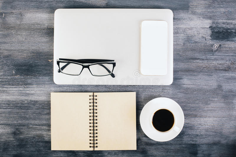 Neatly organized items on table. Dark wooden desktop with neatly organized laptop, coffee cup, notepad, blank white smart phone and glasses. Top view, Mock up stock photography