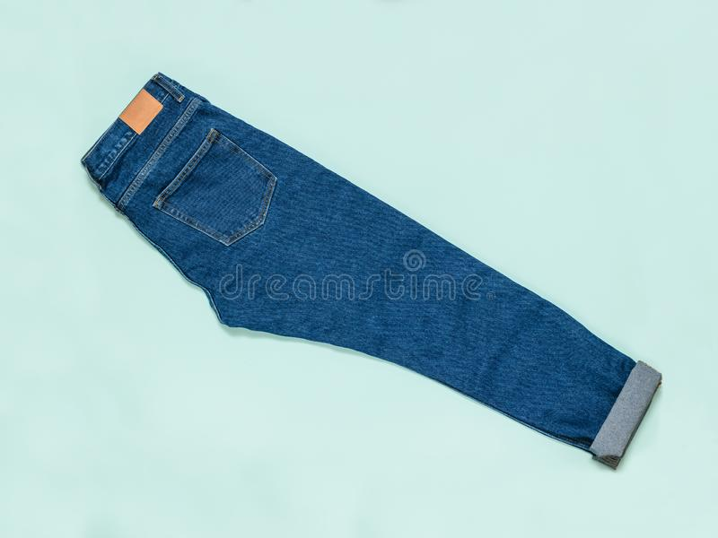 Neatly stacked blue jeans on a blue background. Flat lay. Neatly stacked blue jeans on a blue background. Fashionable denim men`s clothing. Flat lay. The view royalty free stock photography