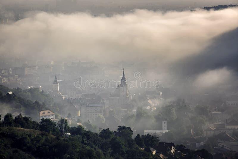 Nebbia sopra la città medievale di Brasov fotografia stock libera da diritti