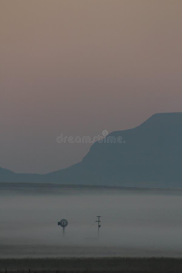 Nebel des frühen Morgens über einem Landwirtfeld mit den Windmühlen und Ernten kaum sichtbar lizenzfreie stockfotos