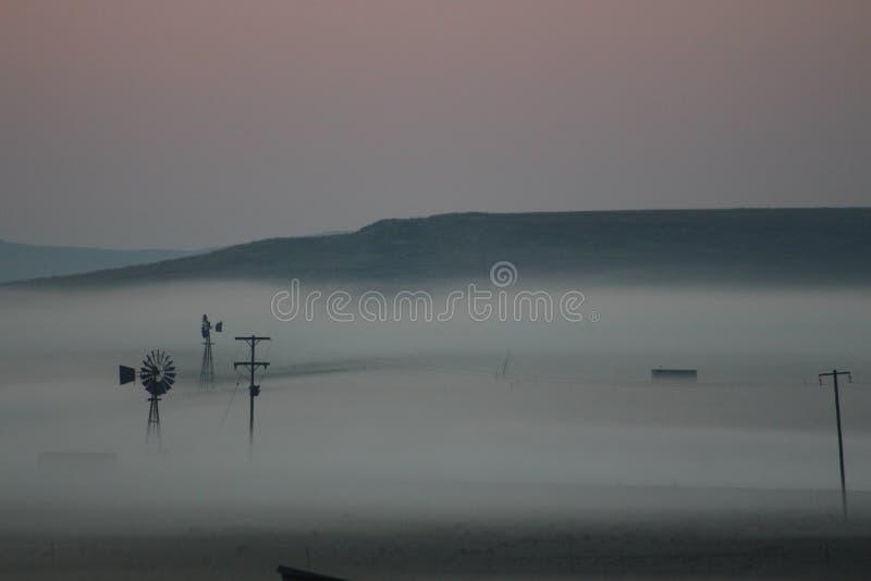 Nebel des frühen Morgens, der einen Bauernhof und die umgebende Landschaft umfasst stockfotos