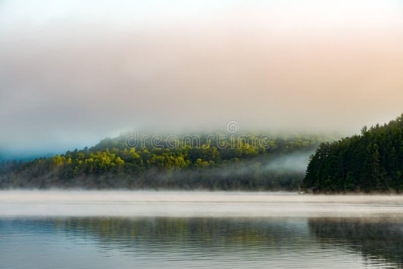 Nebel des frühen Morgens, der vor einem kleinen, reflektierenden See sich klärt lizenzfreie stockfotos
