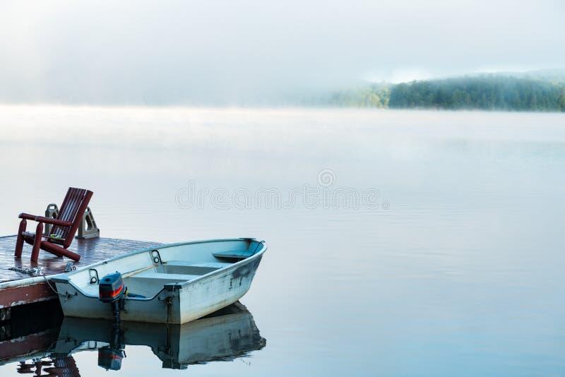 Nebel des frühen Morgens, der vor einem kleinen See sich klärt stockbild