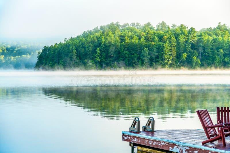 Nebel des frühen Morgens mit Dock und roten Holzstühlen stockfoto