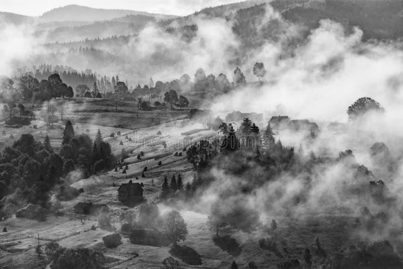 Nebelhafte Karpatendorfhügel nach dem Regen lizenzfreies stockfoto