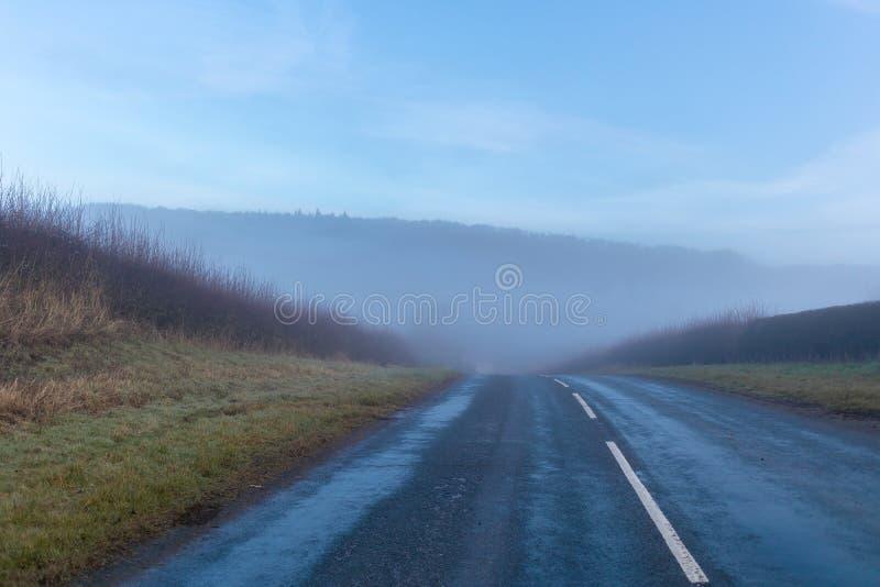 Nebelhafte Straße, die zu überall führt stockbild