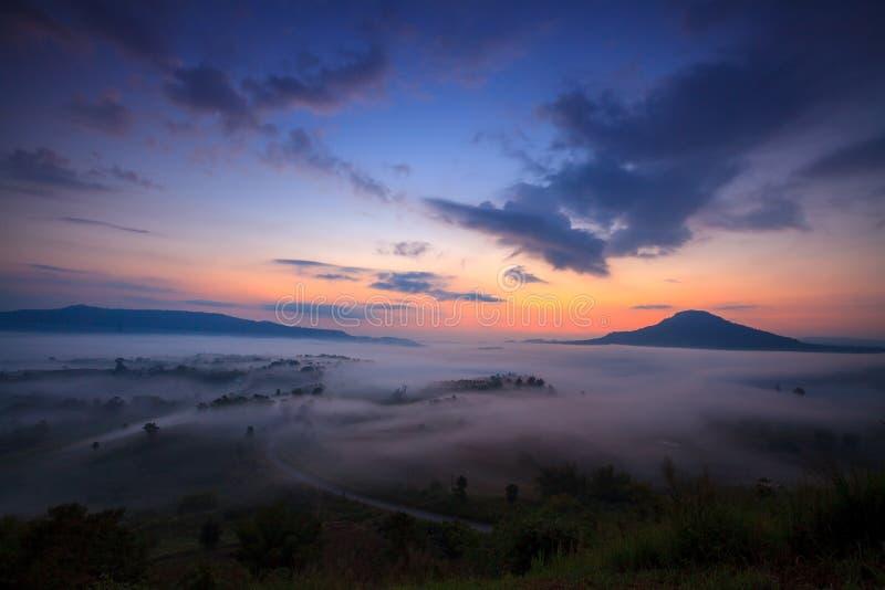 Nebelhafter Morgensonnenaufgang und -straße im Berg bei Khao-kho Phetchabu lizenzfreie stockfotos