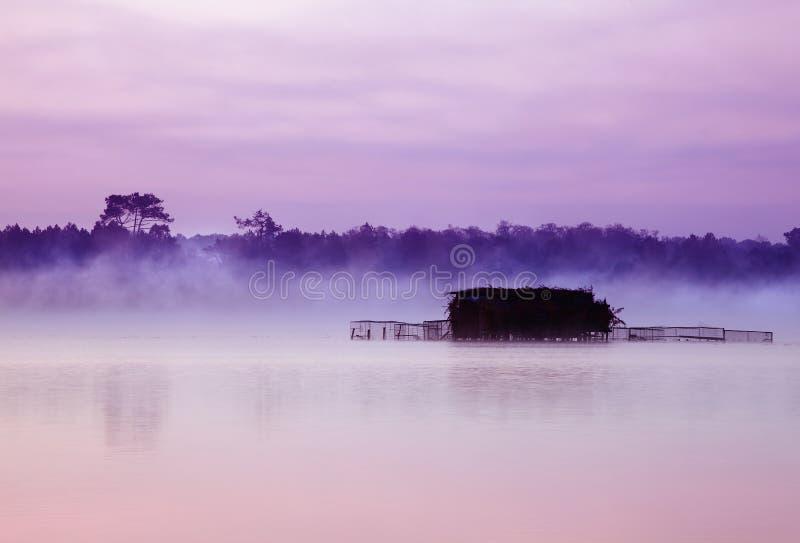 Nebelhafter See und Hütten stockfoto