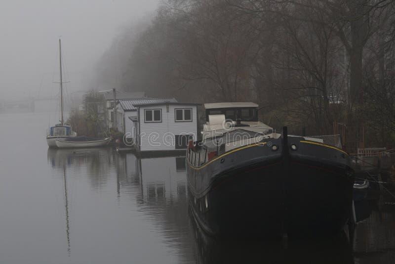 Nebelhafter Tag mit verschiedenen Arten von Hausbooten am Oostennburger-Kanal, Amsterdam die Niederlande stockfoto