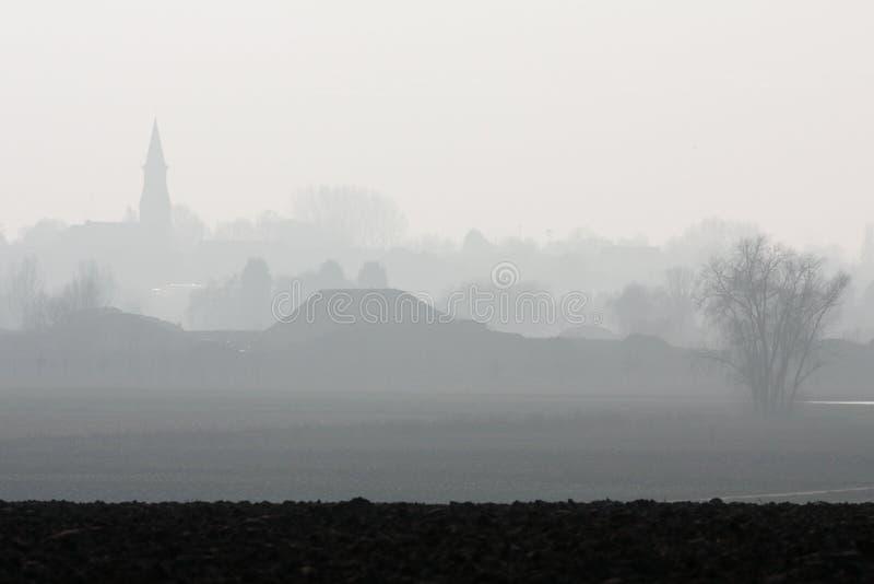 Nebelige Landschaft und Dorf stockfoto