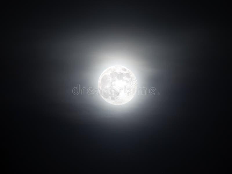 Nebeliger Himmel mit dem hellen Vollmond, der in die Dunkelheit glüht stockfoto