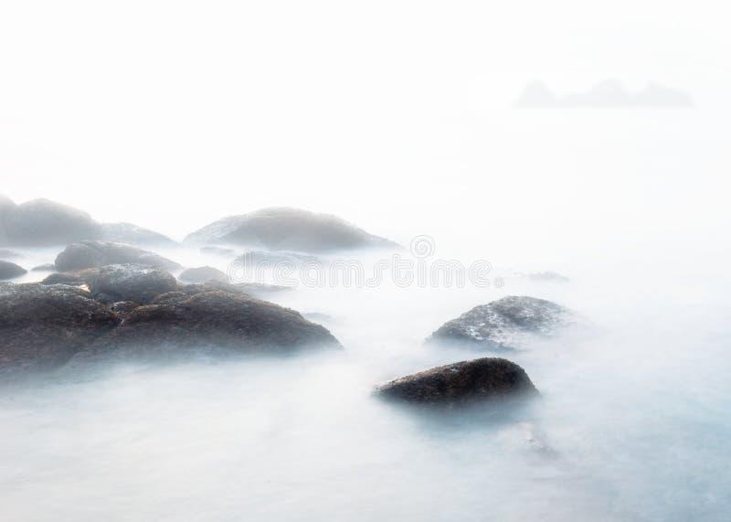 Nebeliger Morgen auf dem Steinstrand stockfotos