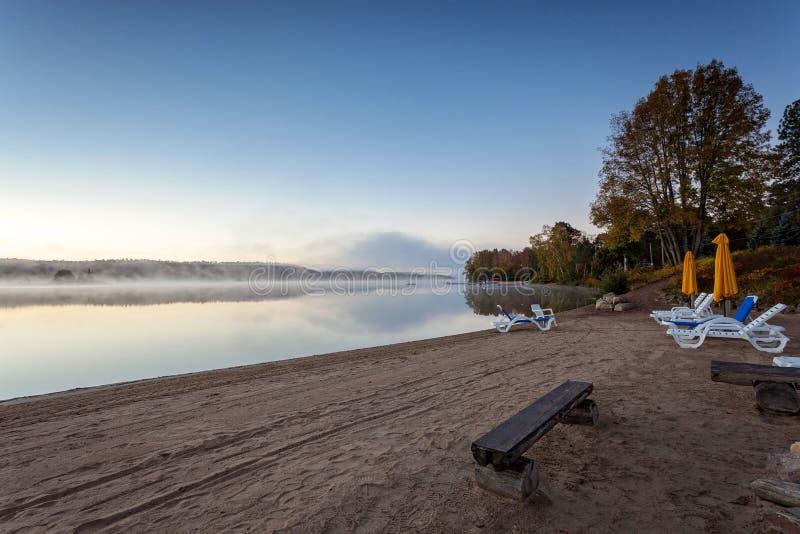 Nebeliger Morgen im See des Algonquin-provinziellen Parks, Ontario, Kanada mit Bänke stockfoto