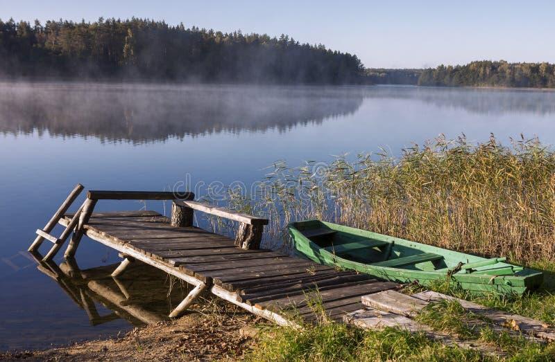 Nebeliger See mit Brücke und Boot lizenzfreies stockbild