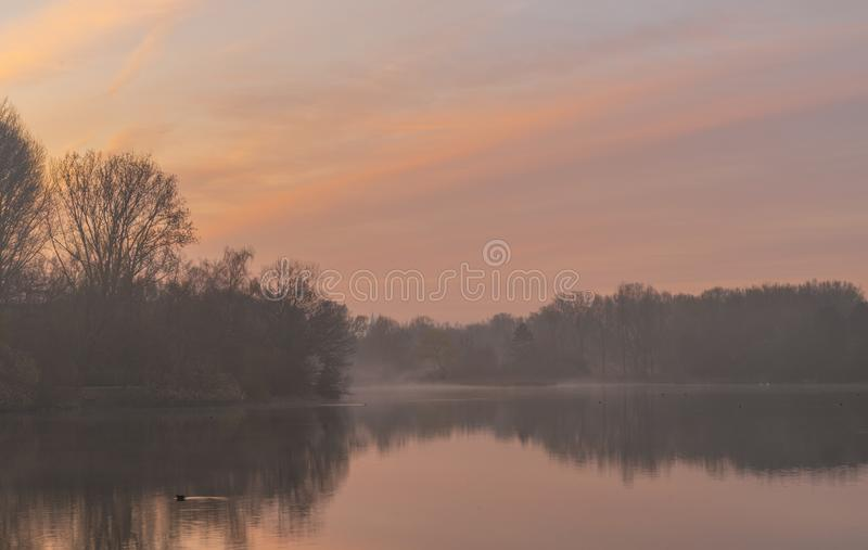 Nebeliger Sonnenaufgang über See stockbild