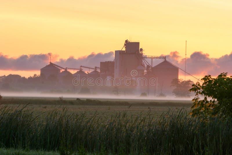 Nebeliger Sonnenaufgang hinter Getreidespeichern in der schlechten Axt, Michigan lizenzfreies stockfoto