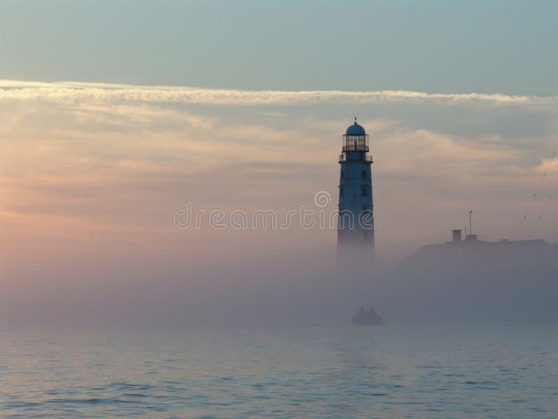 Nebeliger Sonnenuntergang, kleines Boot und Leuchtturm lizenzfreies stockbild