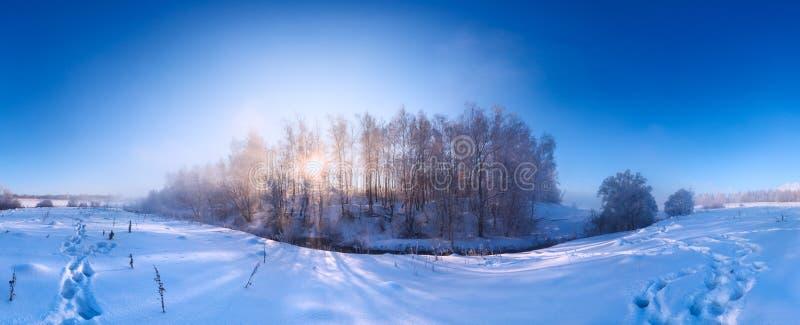 Nebeliger Winterflußufer am Morgenpanorama mit Sonne durch Suppengrün in der Mitte stockfoto