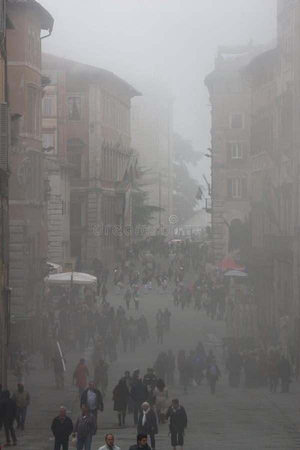 Nebelmorgen in Perugia (Toskana, Italien) Leute-Gehen lizenzfreie stockfotos