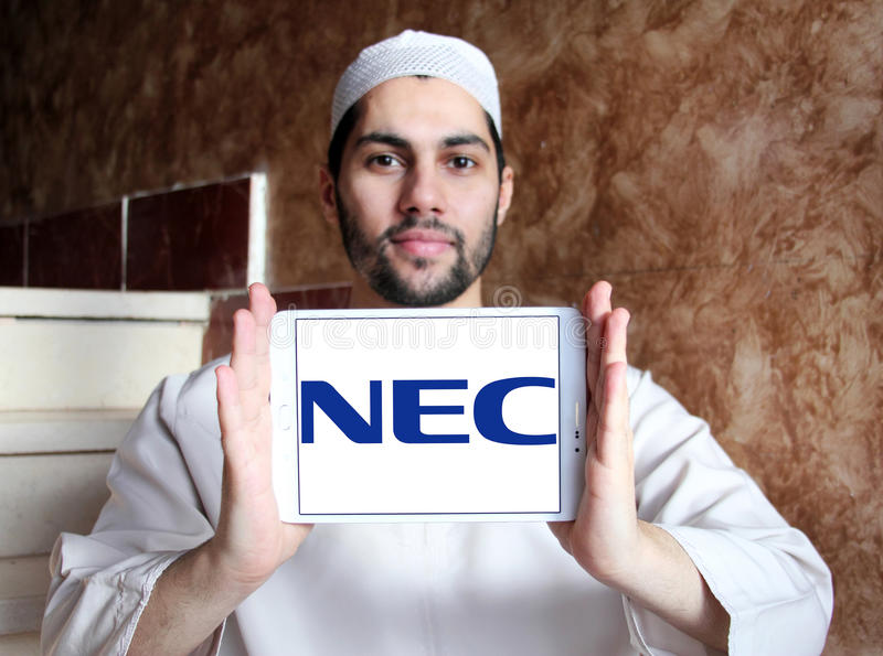 NEC Corporation logo. Logo of NEC Corporation on samsung tablet holded by arab muslim man. NEC Corporation is a Japanese multinational provider of information royalty free stock images