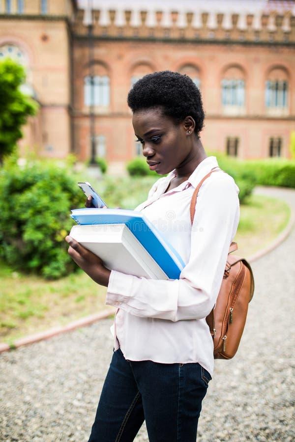 Necesite comprobar una cierta información en Internet Estudiante joven feliz del afroamericano uni que usa el teléfono celular fotografía de archivo