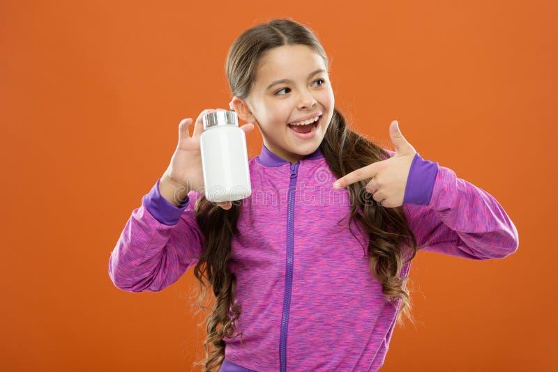 Necesite los suplementos de la vitamina Muchacha linda del niño tomar algunas medicinas Tratamiento y medicina Producto natural N imagenes de archivo