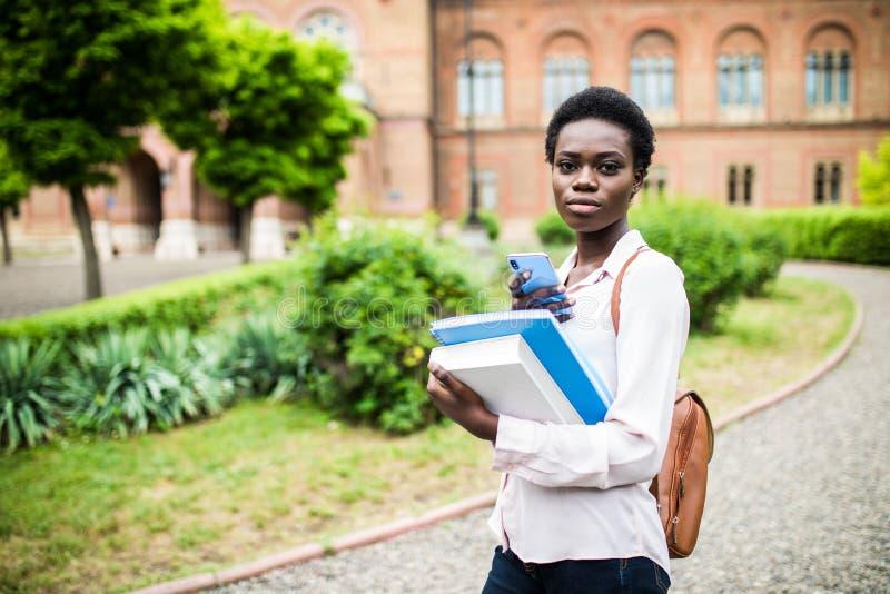 Necesito charlar con mis amigos Estudiante joven feliz del afroamericano uni que usa el teléfono celular fotografía de archivo libre de regalías