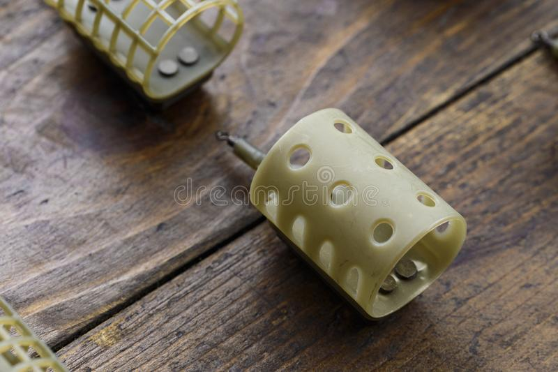 Necessary accessories for feeder fishing on a wooden board. Feeder feeders side view royalty free stock photos