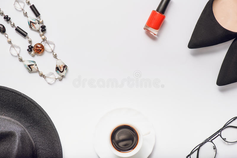 Necessary beautiful accessories for woman. Cup of black coffee in opposite to scarlet nail polish. Glasses near classic female shoes. Top view stock photography