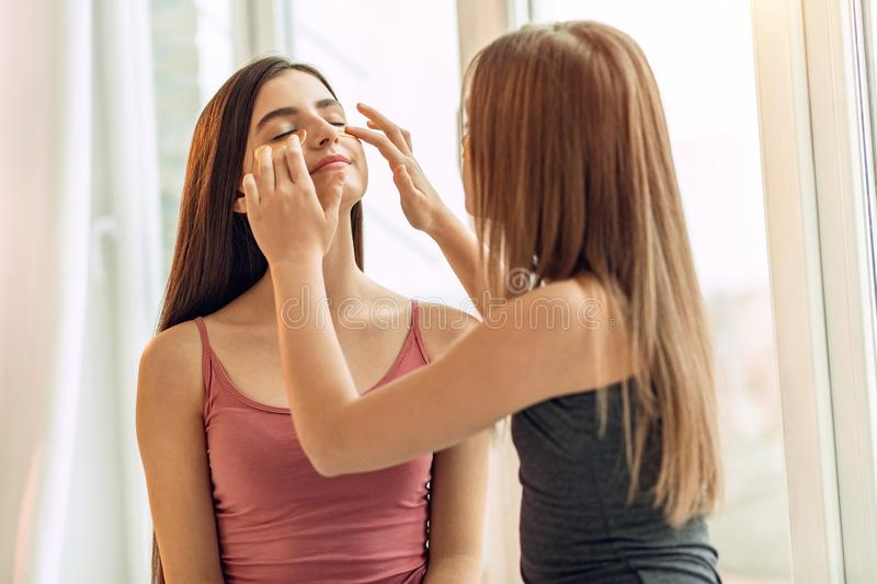 Pleasant girl helping her sister apply under-eye patches royalty free stock photo