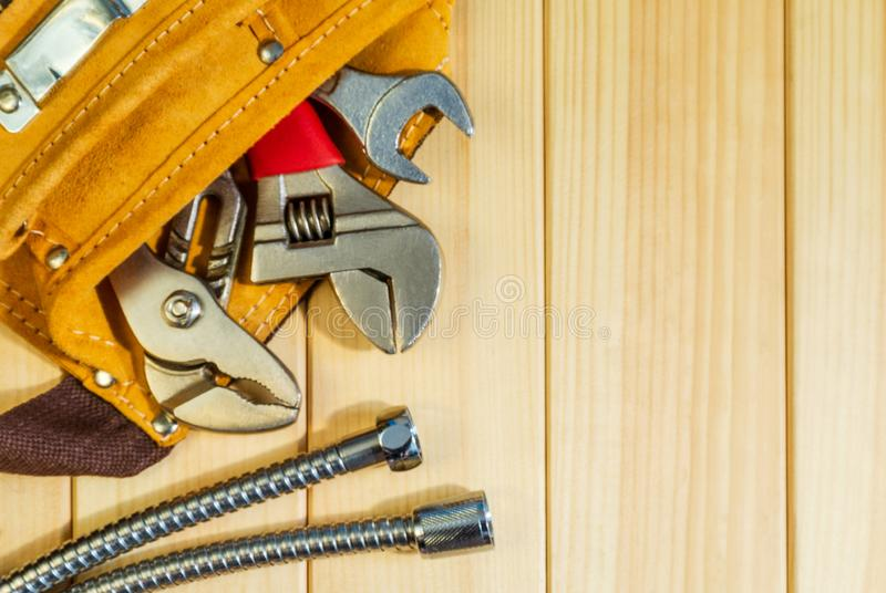 Necessary set of tools in the bag for plumbers on a wooden background. Indispensable for master stock image