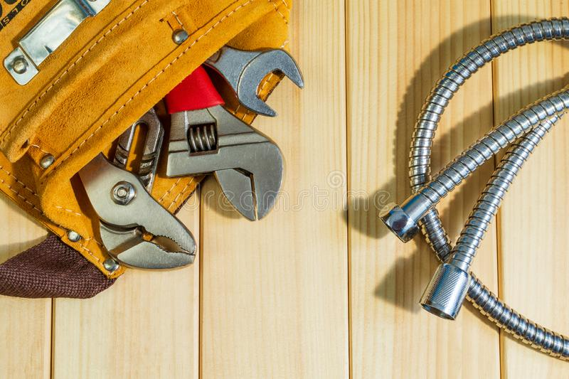 Necessary set of tools in the bag for plumbers on a wooden background. Indispensable for master royalty free stock photography