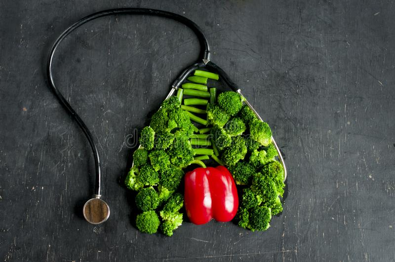 Necessary vegetables for lung and heart health. Broccoli and red pepper lined in the form of lungs and hearts together with a stethoscope on a dark background royalty free stock photos