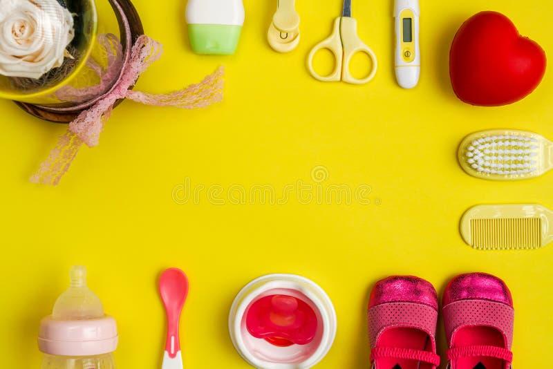 Necessidades e utensílios do cuidado do bebê no fundo amarelo imagens de stock royalty free