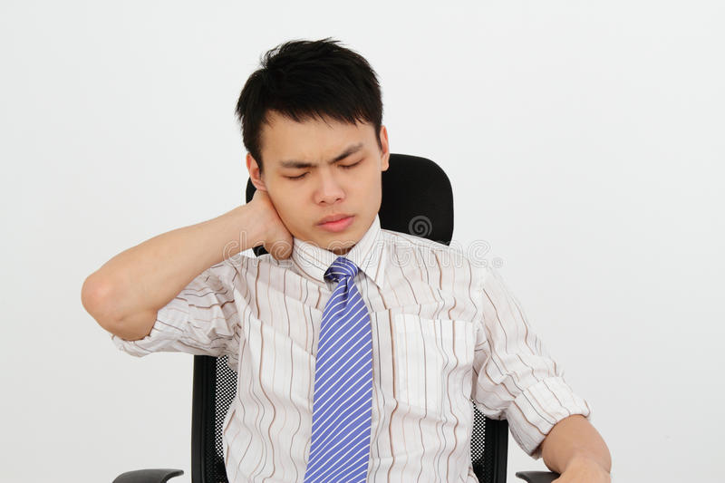 Neck ache. An office worker suffering from neck ache stock photography
