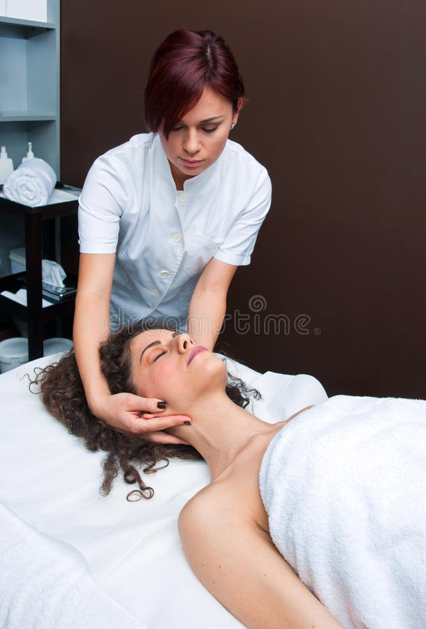 Neck adjustment. Attractive women on massage table in beauty salon having neck adjustment royalty free stock photo