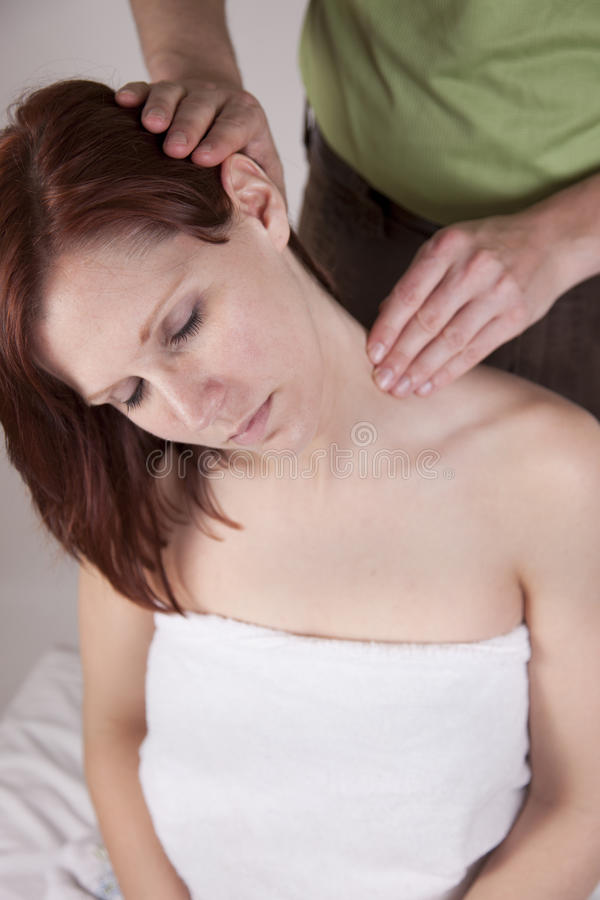 Neck alignment. Attractive young woman receives shoulder a neck alignment or massage from an Osteopath or massage therapist royalty free stock photo