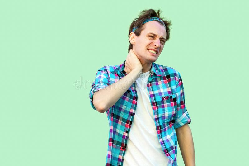 Neck or back pain. Portrait of sad injuried young man in casual blue checkered shirt and headband standing and holding his painful royalty free stock images