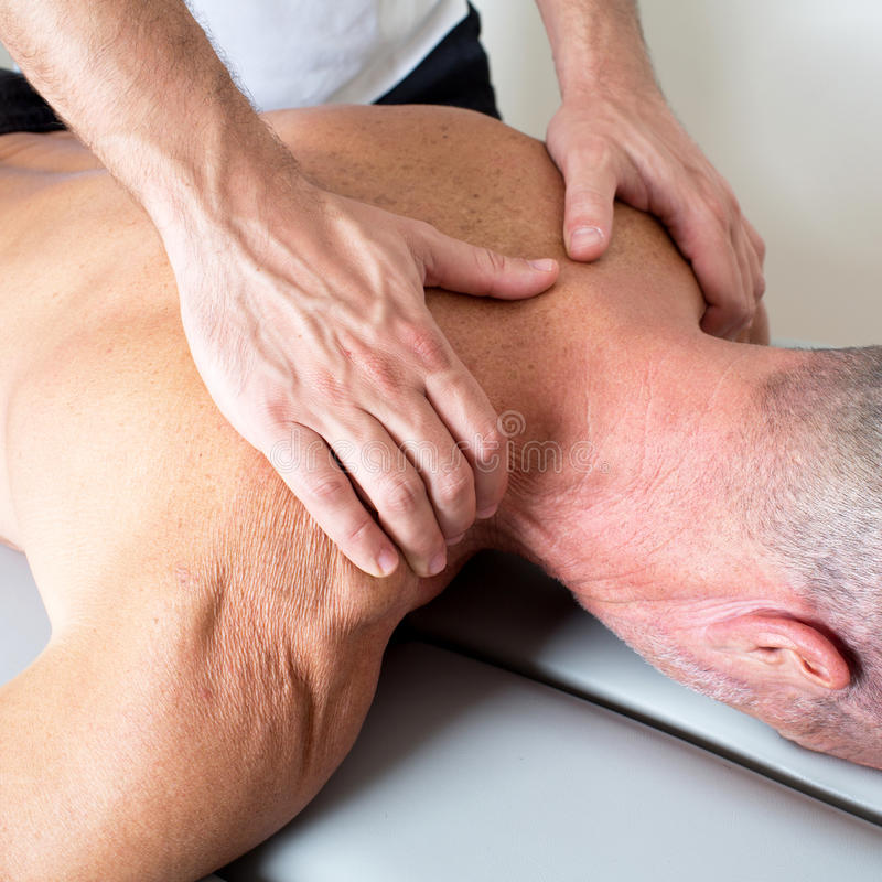 Neck massage. Doctor manipulating the neck of an elderly male patient royalty free stock images