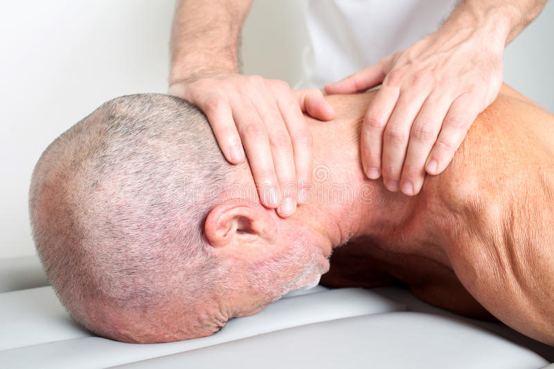 Neck massage. Doctor manipulating the neck of an elderly male patient royalty free stock photography