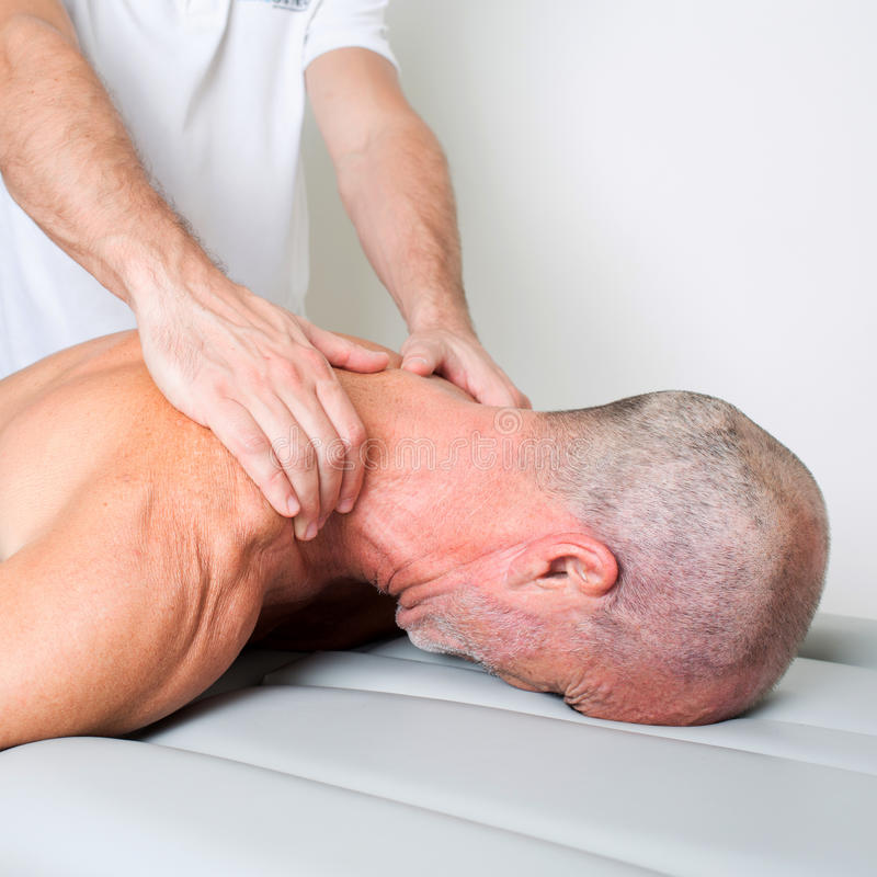 Neck massage. Doctor manipulating the neck of an elderly male patient stock photography
