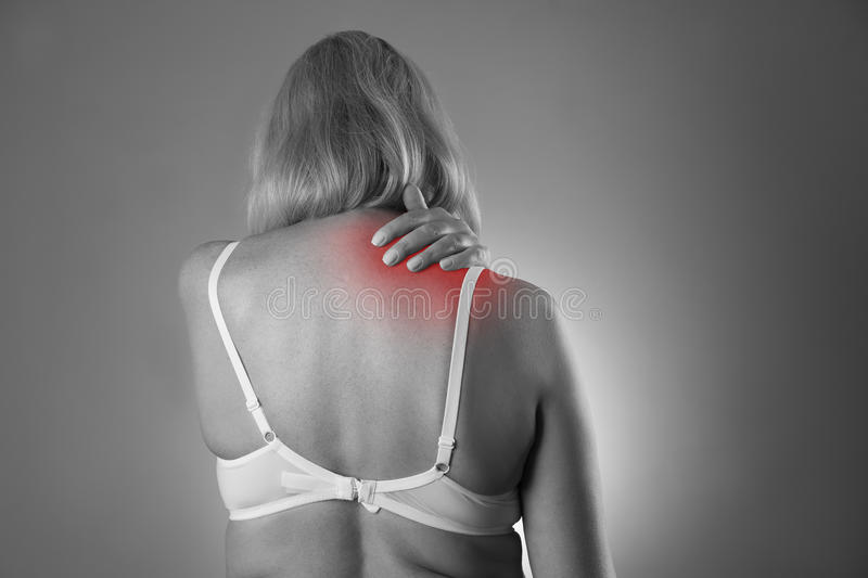 Neck pain, massage of female body, ache in woman`s body. Black and white photo with red spots stock photography