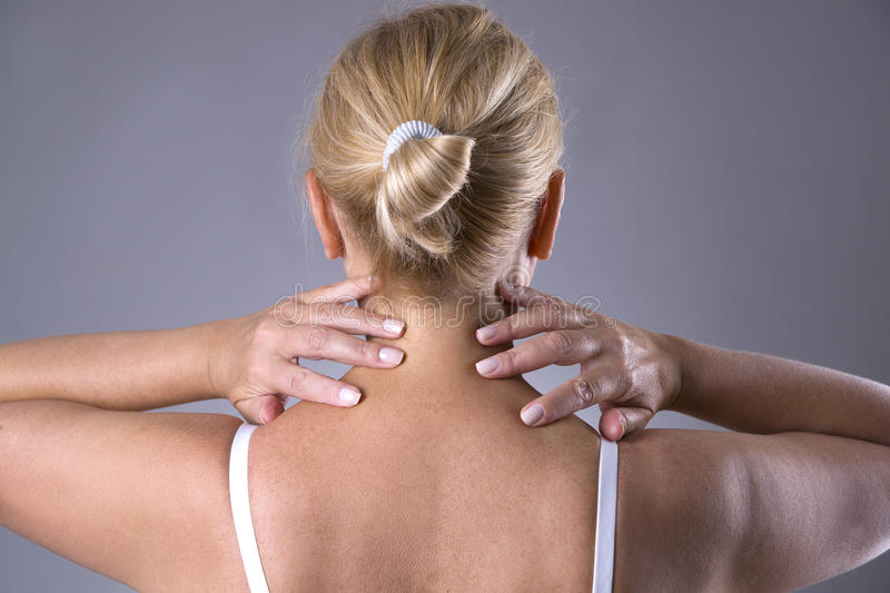 Neck pain, massage of female body, ache in woman`s body. On gray background royalty free stock photos