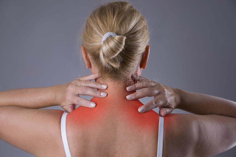 Neck pain, massage of female body, ache in woman`s body. On gray background stock photography