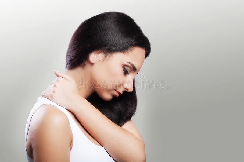 Neck pain. Painful sensations in the neck area. The girl holds her hand to the painful area. Rheumatism The concept of health. On. A gray background royalty free stock photography