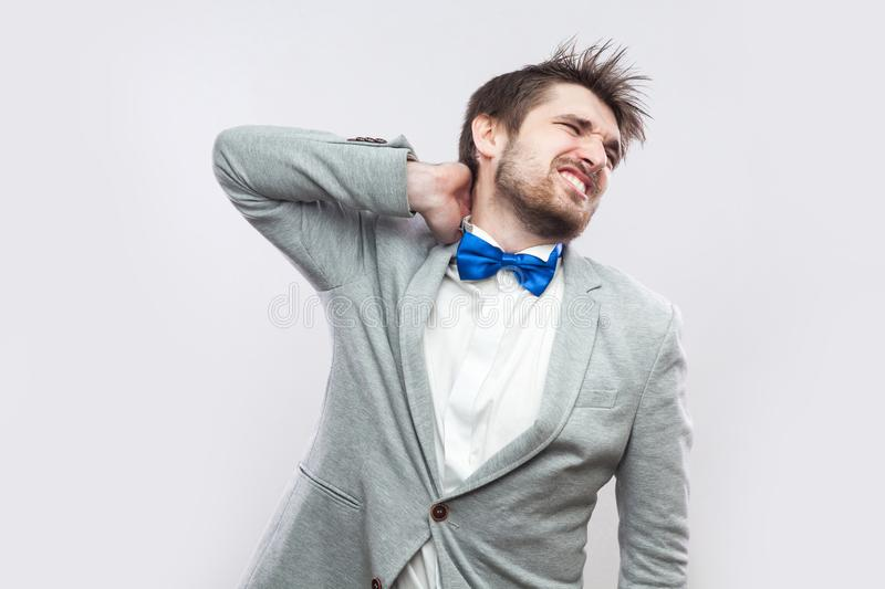 Neck pain. Portrait of handsome bearded businessman in casual grey suit and blue bow tie standing and holding his painful neck royalty free stock image