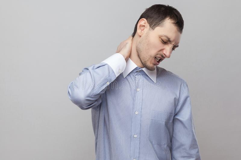 Neck pain. Portrait of handsome bristle businessman in classic light blue shirt standing holding his painful neck and feeling royalty free stock photography