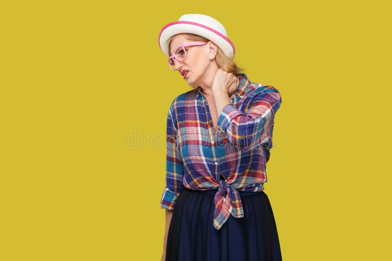 Neck pain. Portrait of sick modern stylish mature woman in casual style with hat and eyeglasses standing and holding her painful. Neck and feeling bad. indoor royalty free stock photos