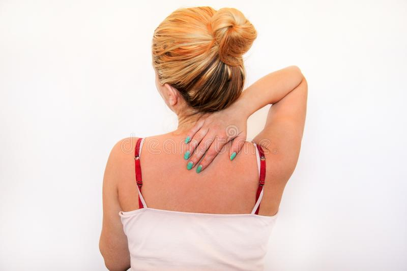 Tired handsome woman having pain in neck, rubbing it. Neck pain. Tired woman having pain in neck, rubbing it. Massage of the shoulder and neck. Pain in the neck stock images